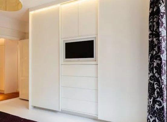 床尾部分对着的墙面设计成简单的电视柜,内嵌式的柜子和电视都不占图片