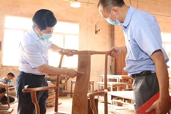 中国传统工艺大师、东成红木董事长张锡复(右一)到车间监督、指导产品工艺