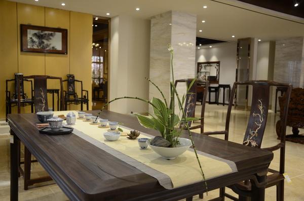 绿植摆放到桌面一角,既能起到装饰作用,又不会挡住红木家具的美(区氏臻品供图)