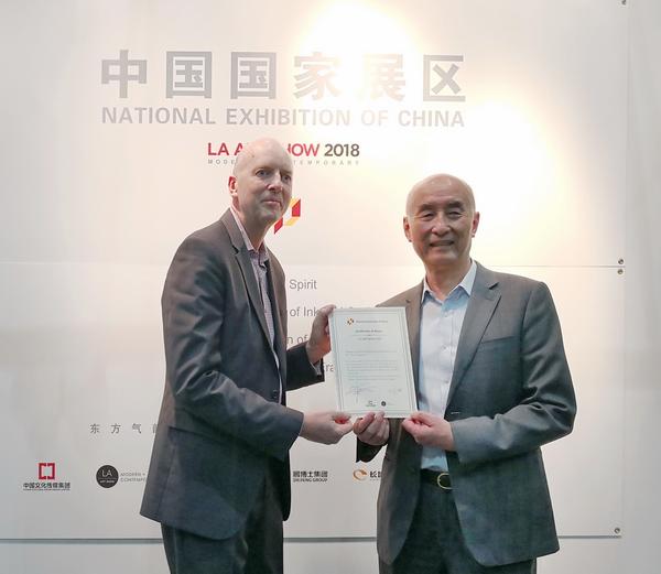 洛杉矶艺博会创始人Kim(左)为中国传统工艺大师、深圳泰和园董事长邵湘文颁发作品纪念证书
