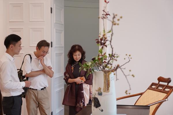 区氏臻品总经理区锦泽(左一)在佳士得秋拍上海预展现场为来宾介绍黄花梨躺椅