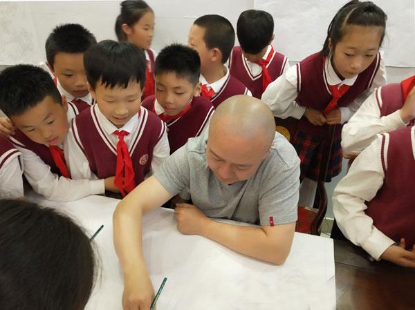 吴宁镇第四小学的学生们围绕在御乾堂红木员工——中国传统工艺美术大师黄志勤身边,看其进行红木家具设计创作
