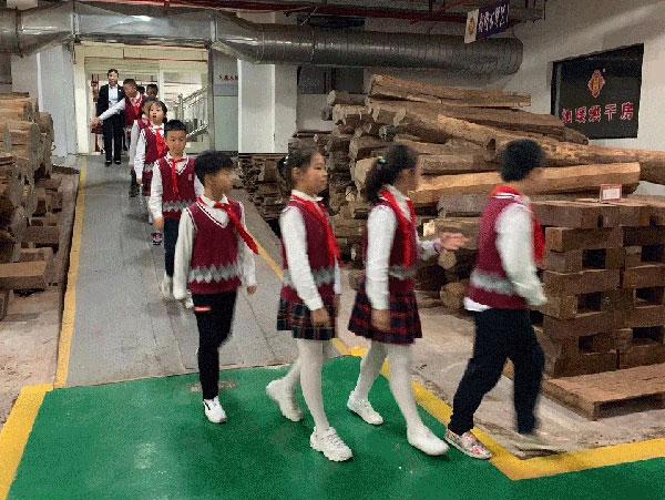 吴宁镇第四小学的师生们走进御乾堂红木生产车间,亲临其境领略红木家具制造魅力