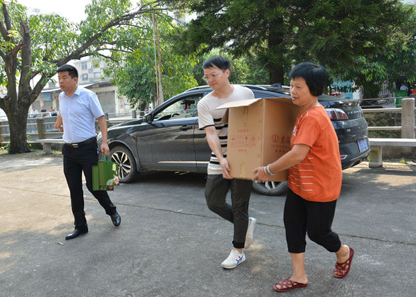 广作红木研究院一行人与敬老院工作人员一同将赠送物资搬进敬老院