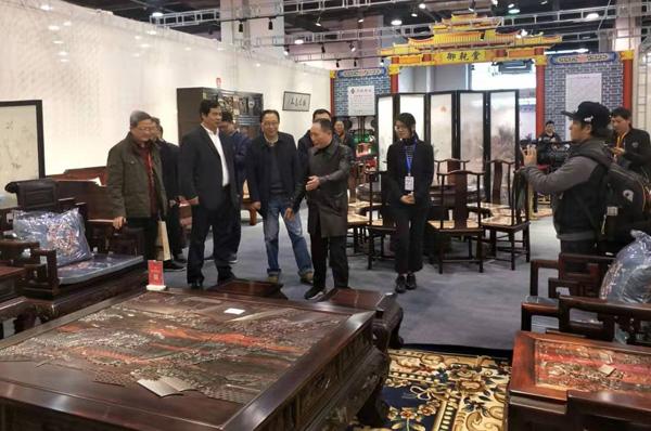 中国林业产业联合会副会长王满(左二)等领导参观御乾堂红木展位,并与马海军董事长(左四)进行交流.jpg