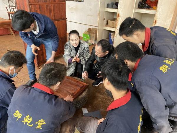 御乾堂红木董事长马海军、总经理马姣姣与木工师傅一起研究小叶紫檀家具的制作工艺