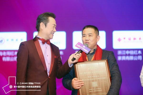 老周家居董事長周仲堅(右)在臺上接受央視主持人趙保樂采訪