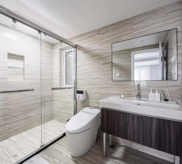卫生间整体通铺石色纹理瓷砖,利用墙面在淋浴房内设计壁龛,可放置
