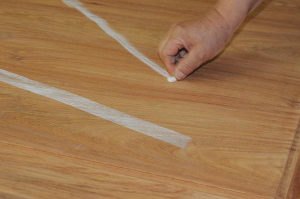 中信红木工匠用粉笔检测刮磨平整度