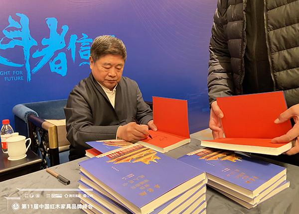 故宫学院院长单霁翔向红木家具企业代表赠书并合影,传递匠心精神