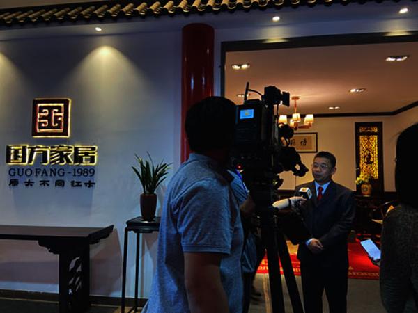中山市大涌镇党委书记王英康在国方家居展位前接受中山电视台的采访.JPG